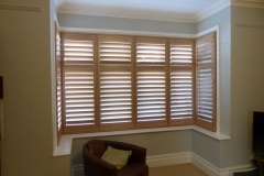 Natural Wood Shutters In Square Bay in Living Room