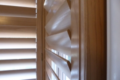 Close Up of Louvre Blades of Natural Wood Shutters in Square Bay Window