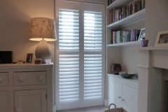 White Plantation Shutters with Middle Rail Fitted to Patio Doors In Lounge