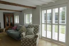 Living Room with White Plantation Shutters Fitted on the Windows and Patio Doors