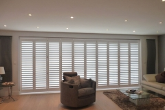 Tracked Shutters Across Wide Doors in Living Room