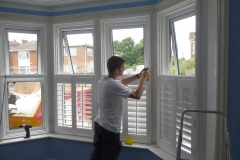 Sam installing shutters on a bay window for 60 minute make over