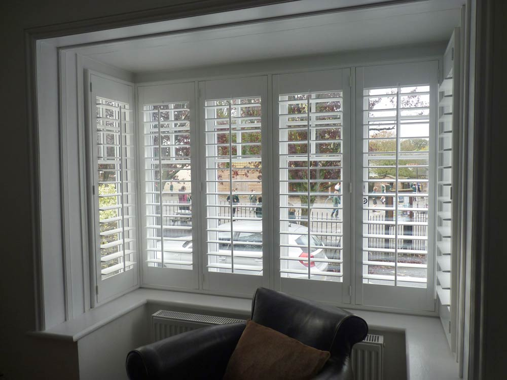 Square bay window fitted with matching wooden shutters