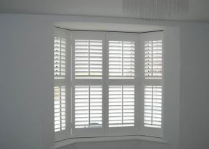 Fauxwood plantation shutters fitted to a UPVC bay window.