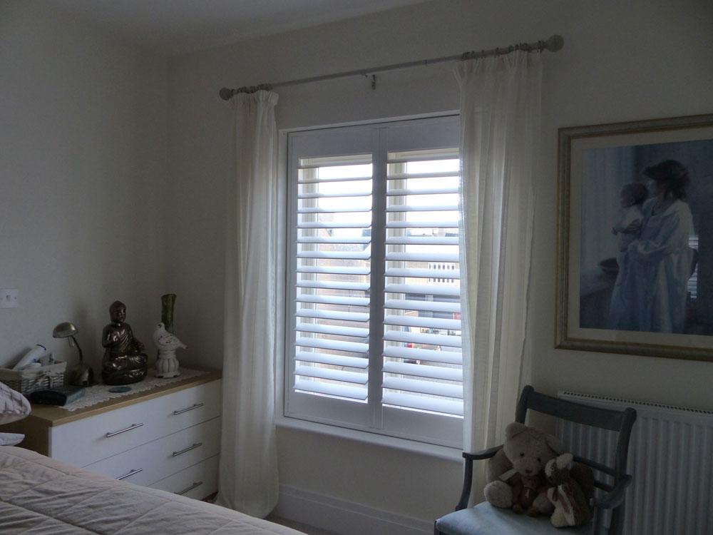 Full Height White Shutters in Bedroom Window