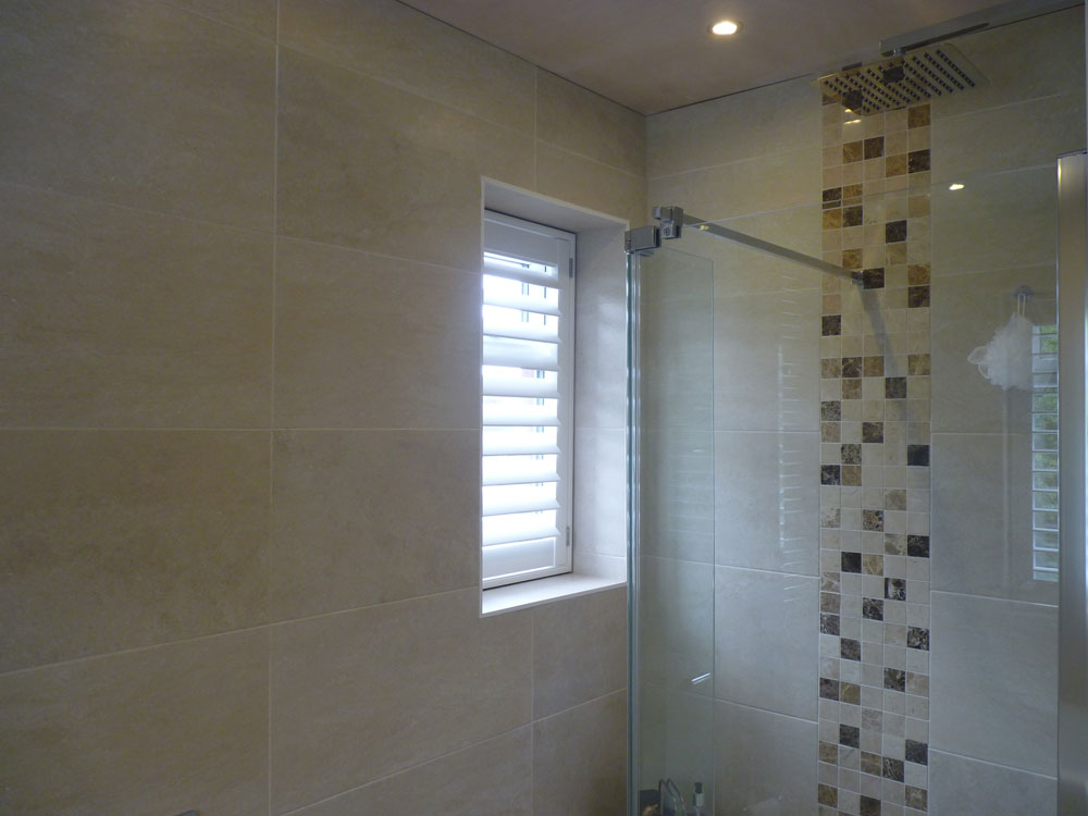 Small Single Window Next to Shower in Bathroom with White Shutter Fitted